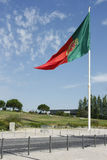 Flagga av Portugal som vinkar, mot blå himmel Arkivfoton