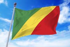 Flagga av Republiken Kongo som framkallar mot en klar blå himmel Royaltyfria Foton