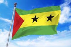 Flagga av Sao Tomé och PrÃncipe som framkallar mot en klar blå himmel Arkivfoto