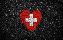 Flagga av Schweiz, schweizisk flagga, hjärta på den svarta bakgrunden, stenar, grus och singel, texturerad vägg royaltyfria foton