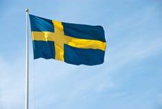 Flagga av Sverige i den blåa skyen Royaltyfria Bilder