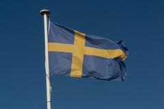 Flagga av Sverige mot blå himmel Royaltyfri Fotografi