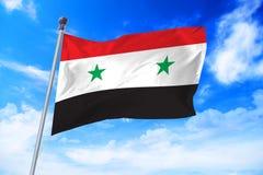 Flagga av Syrien Arabrepubliken Syrien som framkallar mot en blå himmel Arkivbild