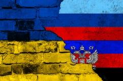 Flagga av Ukraina och Donetsk och republiken för Lugansk folk` s på en texturerad tegelstenvägg Fotografering för Bildbyråer
