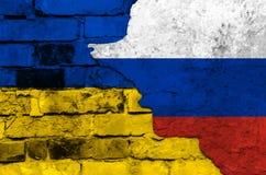 Flagga av Ukraina och Ryssland på en texturerad tegelstenvägg Royaltyfria Foton