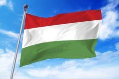 Flagga av Ungern som framkallar mot en klar blå himmel Arkivbilder