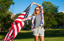 Flagga för Förenta staterna för ung lycklig patriotkvinna hållande Royaltyfri Fotografi