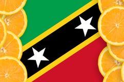 Flagga för helgon Kitts och Nevis i vertikal ram för citrusfruktskivor royaltyfri bild