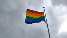 Flagga för LGBT-regnbågestolthet som vinkar på vind på molnig brittisk himmelbakgrund i northampton England royaltyfria foton