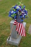 Flagga och blommor på gravstenen Royaltyfri Fotografi