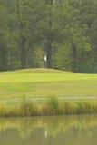 Flagga och det gröna golffältet Arkivbild