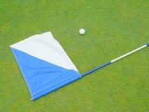 Flagga och golfboll arkivbilder