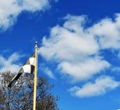 Flagga och moln för sista varv arkivfoto