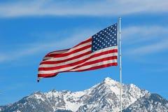 Flagga ovanför det snöig Utah berget Arkivfoto