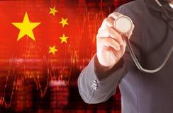 Flaggan av data för det Kina downtrendmaterielet diagram med affärsmannen som rymmer en stetoskop Fotografering för Bildbyråer