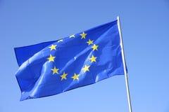 Flaggan av Europa eller det europeiska flaggaflyget i blå himmel arkivfoton