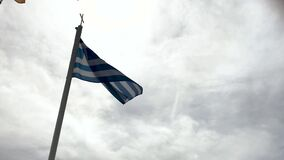 Flaggan av Grekland fladdrar i vinden mot bakgrunden av himlen stock video