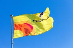 Flaggan av oljebolag Rosneft mot blå himmel Royaltyfri Fotografi