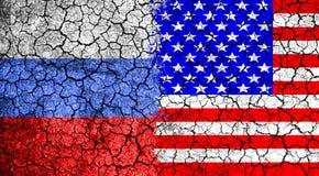Flaggan av Ryssland och USA målade på den spruckna väggen Begrepp av kriget kalla kriget Kapprustningen Kärn- krig Royaltyfri Bild