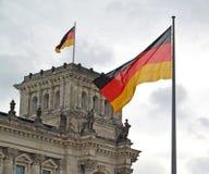 Flaggan av Tysklandfladdranden mot bakgrunden av den Reichstag byggnaden berkshires royaltyfria bilder