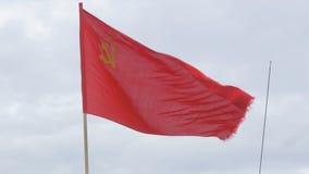 Flaggan av USSR som framkallar i vinden på en flaggstång i en blåsig dag Flagga av Sovjetunionenet mot himlen Arkivbild