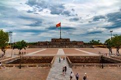 Flaggatorn i ton, Vietnam, med dramatiska moln och turister i forgrounden royaltyfri fotografi