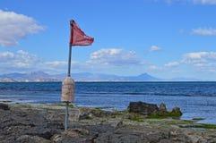 Flagge auf dem Strand Stockbild