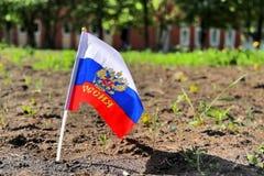 Flagge in den Farben von Russland mit Emblem auf natürlichem Hintergrund Stockbild