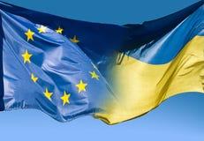 Flagge der Europäischer Gemeinschaft und Flagge von Ukraine Stockfotografie