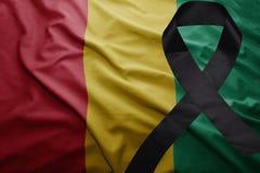 Flagge der Guine mit schwarzem Trauerband stockbilder