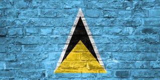 Flagge der St. Lucia über einem alten Backsteinmauerhintergrund, Oberfläche stockbild