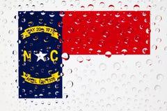 Flagge des amerikanischer Staats-North Carolina hinter einem umfassten Glasesprit Stockfotos