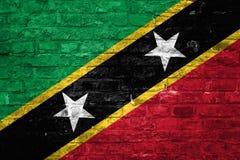 Flagge des Heiligen Kitts und Nevis über einem alten Backsteinmauerhintergrund, Oberfläche lizenzfreies stockbild