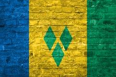 Flagge des Heiligen Vincet und die Grenadinen über einem alten Backsteinmauerhintergrund, Oberfläche stockfotos