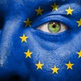 Flagge gemalt auf Gesicht mit grünem Auge, um Europa-Unterstützung zu zeigen Lizenzfreie Stockbilder