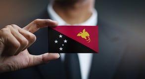 Flagge Geschäftsmann-Holding Card Papuas Neu-Guinea stockbilder