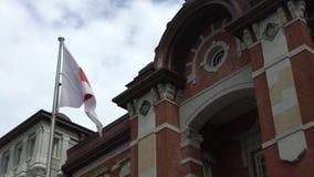 Flagge 4K von Japan wellenartig bewegend in Wind an Tokyo-Station Bahnhof Marunouchi stock video