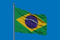 Flagge von Brasilien wellenartig bewegend in den Wind gegen tiefen blauen Himmel Brasilianische Markierungsfahne lizenzfreie abbildung
