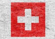 Flagge von der Schweiz über Backsteinmauer Stockbilder