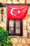 Flagge von der Türkei über dem Fenster des Steinhauses Lizenzfreie Stockbilder