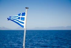 Flagge von Griechenland wellenartig bewegend über blaues Meerwasser Lizenzfreie Stockfotos