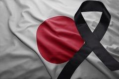 Flagge von Japan mit schwarzem Trauerband Stockbilder