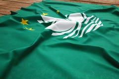 Flagge von Macau auf einem h?lzernen Schreibtischhintergrund Draufsicht Seiden-Macao-Flagge lizenzfreie stockbilder