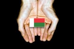 Flagge von Madagaskar in den Händen auf schwarzem Hintergrund Stockbild