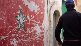 Flagge von Marokko mit einer grünen Sternflagge von Marokko auf Straßenwand in Essaouira Medina Lokale Leute überschreiten vorbei stock video