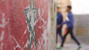 Flagge von Marokko mit einer grünen Sternflagge von Marokko auf Straßenwand in Essaouira Medina Lokale Leute überschreiten vorbei stock footage