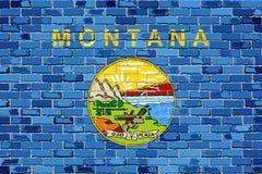 Flagge von Montana auf einer Backsteinmauer Stockbilder
