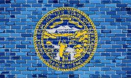 Flagge von Nebraska auf einer Backsteinmauer Lizenzfreie Stockbilder