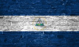 Flagge von Nicaragua über einem alten Backsteinmauerhintergrund, Oberfläche stockfoto