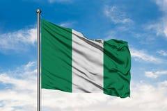 Flagge von Nigeria wellenartig bewegend in den Wind gegen wei?en bew?lkten blauen Himmel Nigerische Markierungsfahne stockfotografie